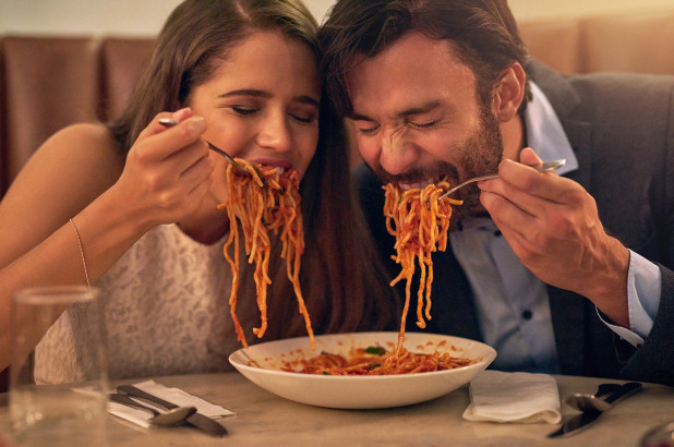 Man and woman sharing a plate of spaghetti