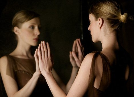 Woman looking at her own reflection