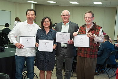 This image shows Professor Semm with his colleagues as they display various certificates.