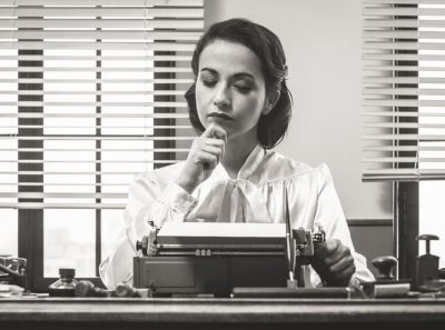 Female playwright writing with a vintage typewriter