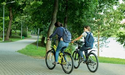 Two student riding their bicycles inside the campus