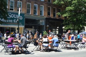 People enjoy discounted food at outdoor tables on Broad Sreet, Richmond.