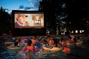 People watching a movie in a pool.