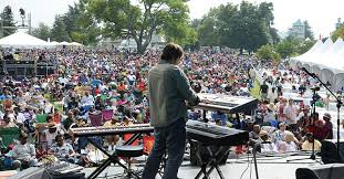 Picture of person using keyboards while on stage in front of crowd