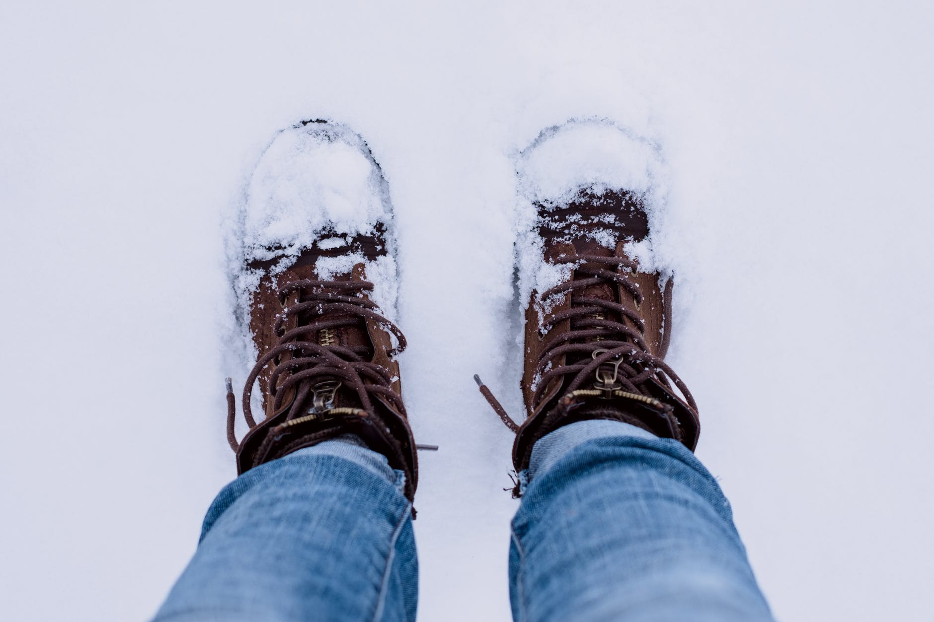 standing in the snow with snow on snow boots