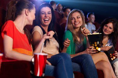 Four girl friends having fun at the cinema