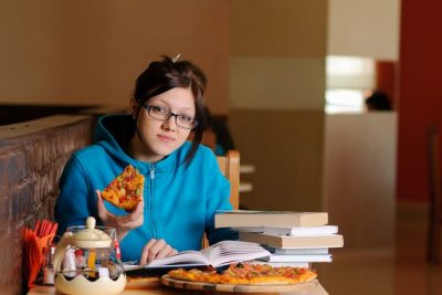 Female student studying while having some pizza