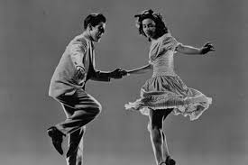 A vintage black-and-white image of a couple swing dancing