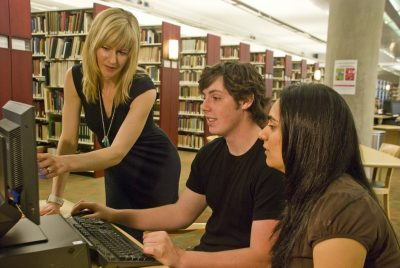 Librarian assisting two students