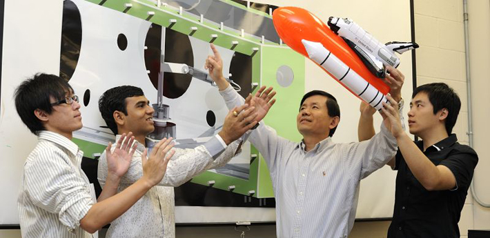 Four people talk in a group while one holds a model rocket.