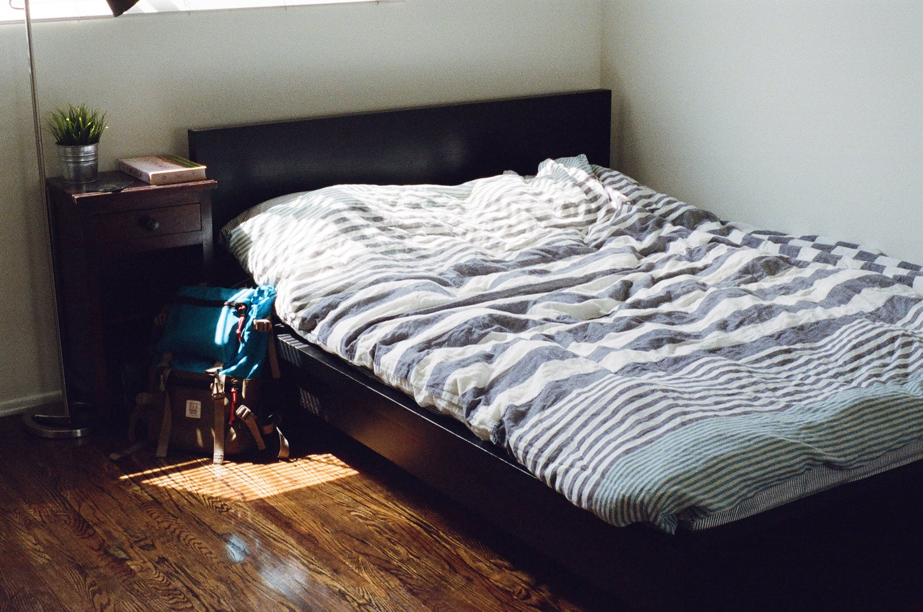 Bed made with comforter and bed side table