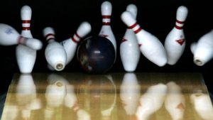 a bowling ball knocking over pins at the bowling alley