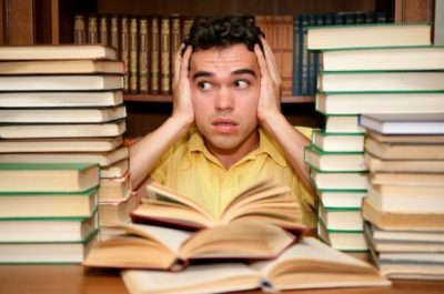 Male student with piles of books in front of him