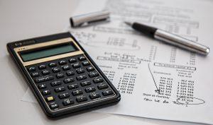 A calculator, an open pen and a financial statement