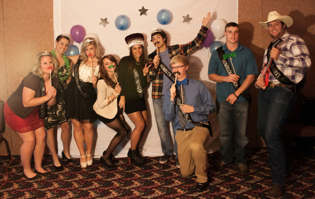 Group of people posing with props for a fun semi formal picture.