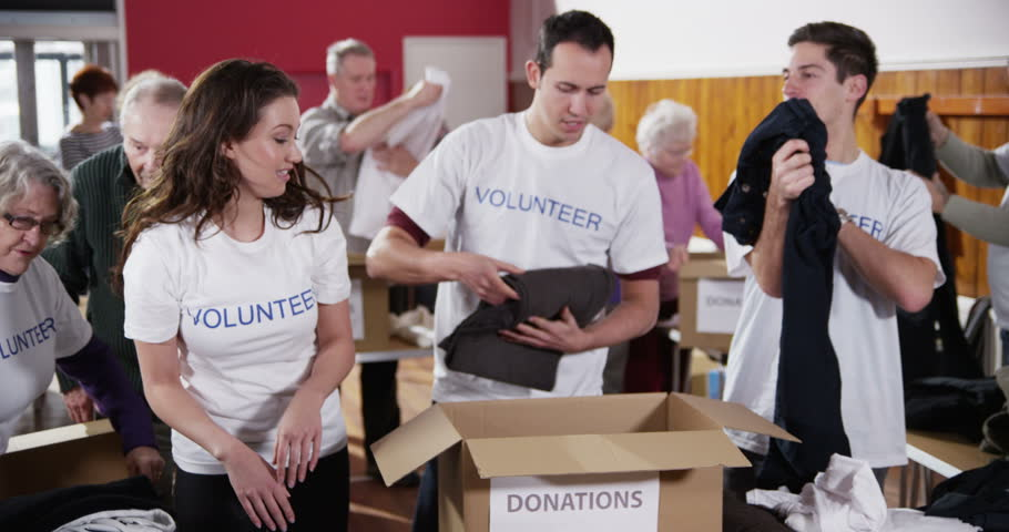 volunteers folding clothes to put in donation box
