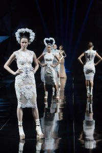 Models walking in a fashion show wearing white