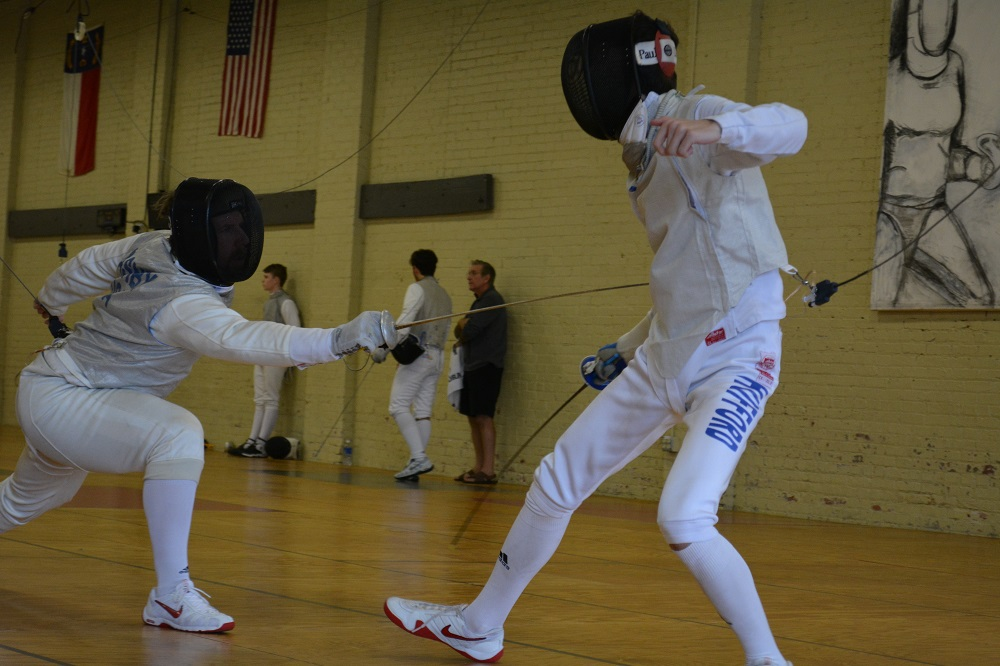 Two people partake in a fencing match.