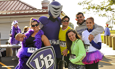 People in colorful outfits pose with the Purple Knight mascot.