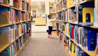 Little girls browsing through bookshelves