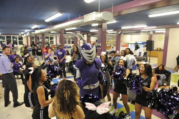 Cheerleaders cheer in a circle around the mascot, Purple Knight.