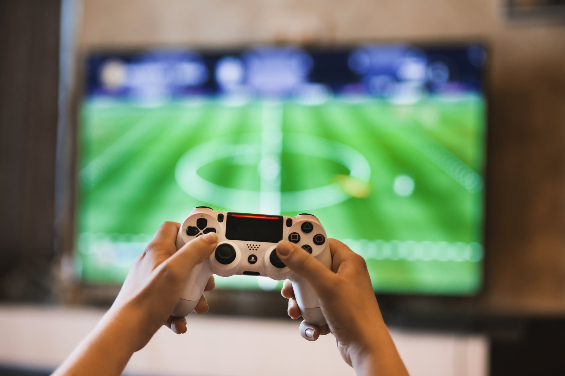 person holding game controller in front of tv