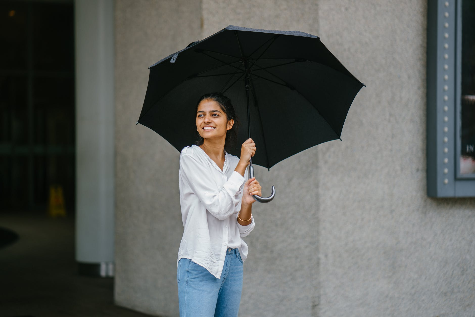 photo of woman wearing white long sleeved shirt and blue jeans holding black umbrella