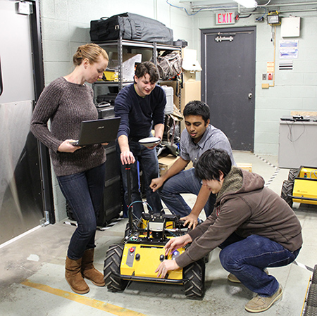 Four people work on a robot.