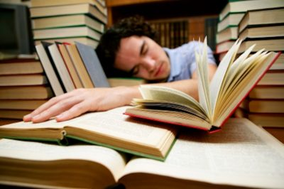 Male student sleeping on his books