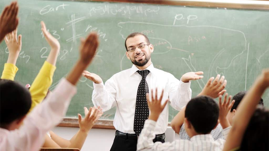 A professor making a question in a classroom and all the students are raising their hands to answer