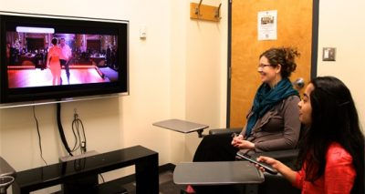 Female students watching on a flat screen TV