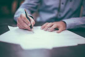 A person writing with a pen in white paper