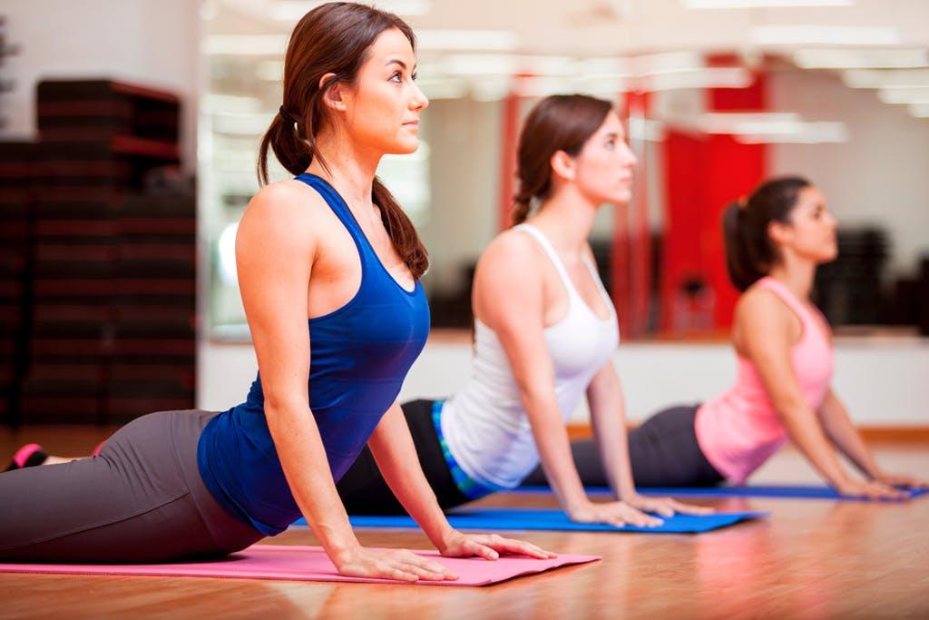 Three people participate in yoga.