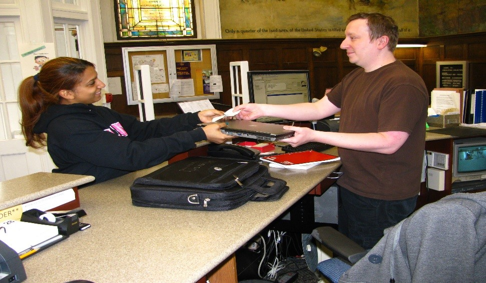 A student borrowing a library laptop