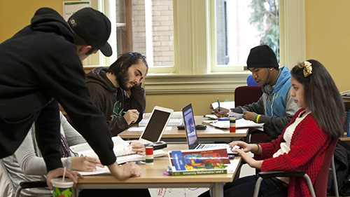 Tutor offering writing services to students in the library