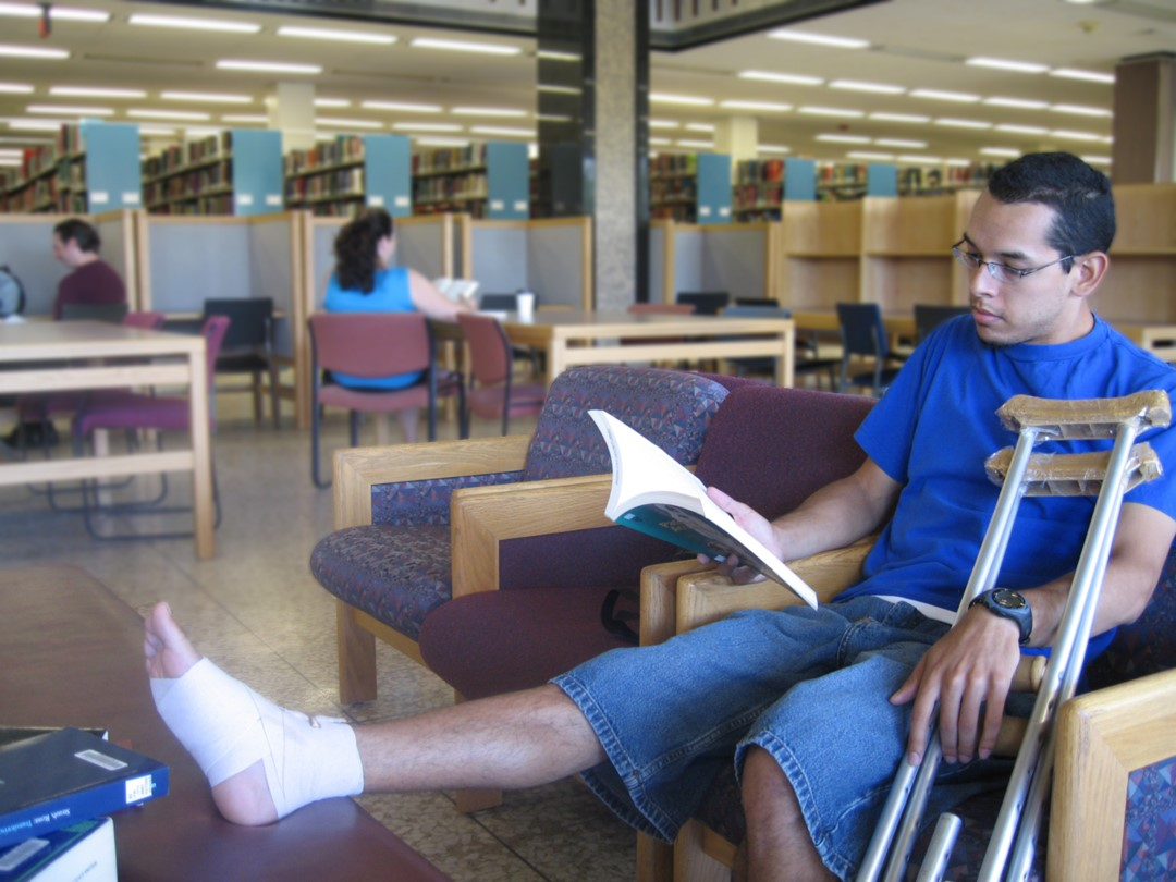 A photo of a student with crutches reading a book