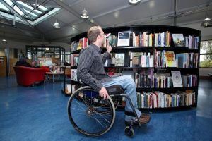 a person in a wheel chair accessing a library