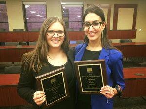 Two students holding plaques
