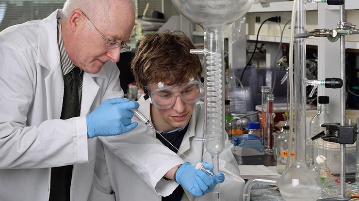 Professor helps student in lab.