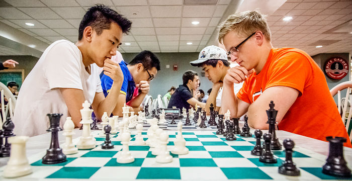 four students playing chess against each other