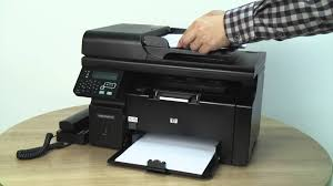 A close-up photo of a hand aperating a printer