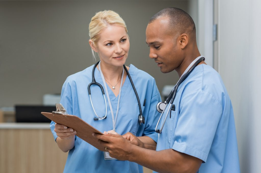 Image of a Female and African-American Nurse Looking at a Clipboard