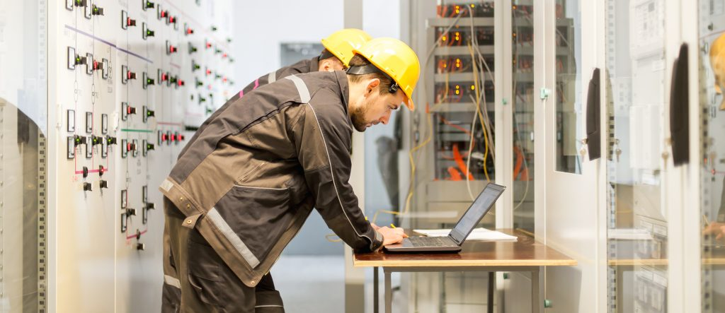 Image of Two Electrical Engineers Bent Over Looking at a Laptop