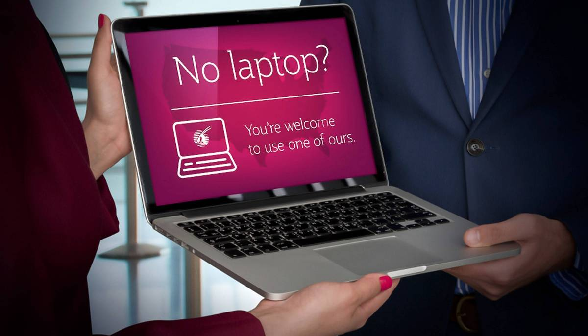 A laptop held by hand with the screen displaying the laptop loaning services at the library.