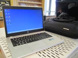 A laptop on a desk displaying a blue screen