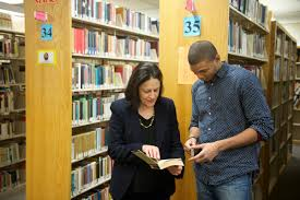 A student getting instructions from a librarian
