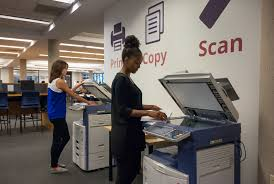 Students operating printers at the library