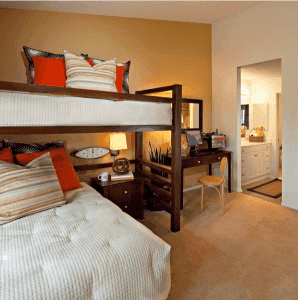 Bunk bed next to desk and bathroom