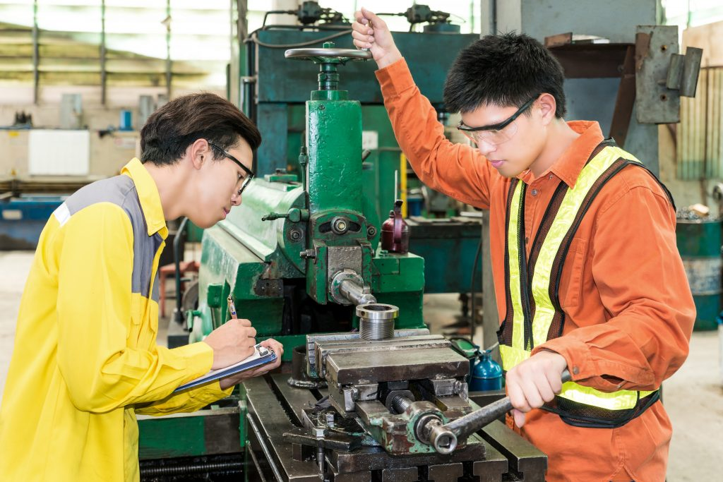 Two Asian Male Mechanical Engineers Inspecting Machinery