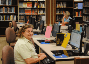 a photo of a librarian using the library computer